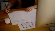 Young Female Architect Studying Plans In Office on blueprint video