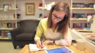 Young female architect working in a library shop using digital tablet and booknote. video
