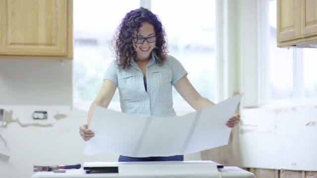 Young female architect working on blueprints of home video