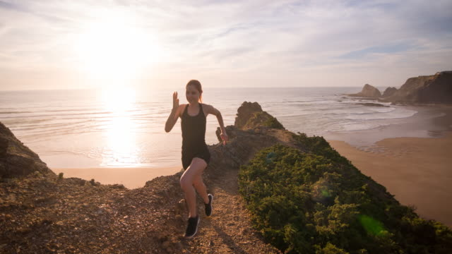 Young female athlete running on a rocky terrain by ocean video