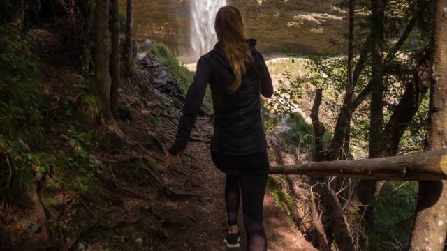 Young female athlete running through the woods towards a waterfall video
