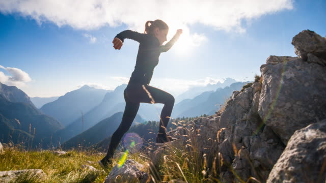 Young female athlete running up the mountain video