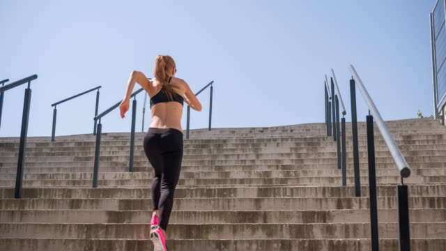 Young female athlete running up the stairs video
