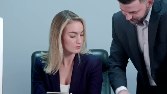 Young female boss sitting at workplace and reading paper with caucasian colleague in office video