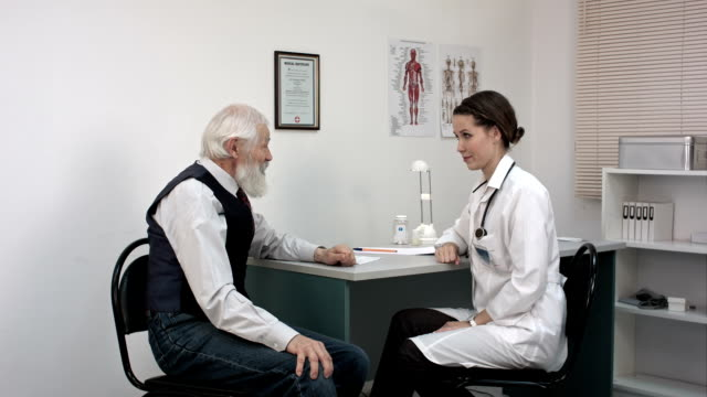 Young female doctor showing showing patient an international certificate video