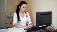 Young female doctor with stethoscope sitting at the table and typing video