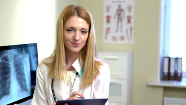 Young Female Doctor Working With Medical Notes And Smiling At The Camera. video