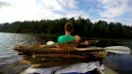 Young female having rest on kayak. Tourism, camping, vacation video
