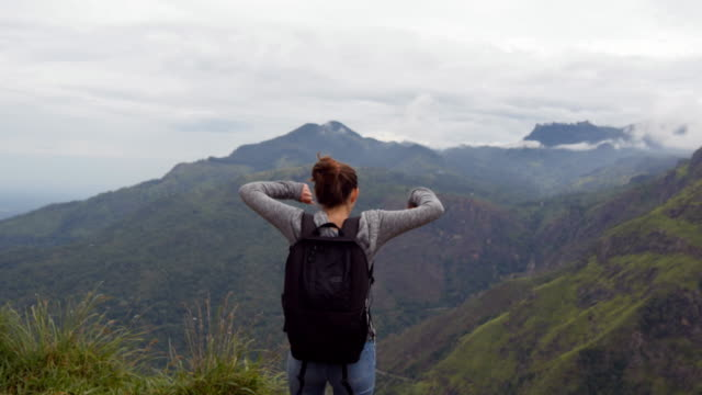 Young female hiker with backpack reaching up top of mountain and raised hands. Woman tourist standing on the edge of beautiful canyon, victoriously outstretching arms up. Rear back view video