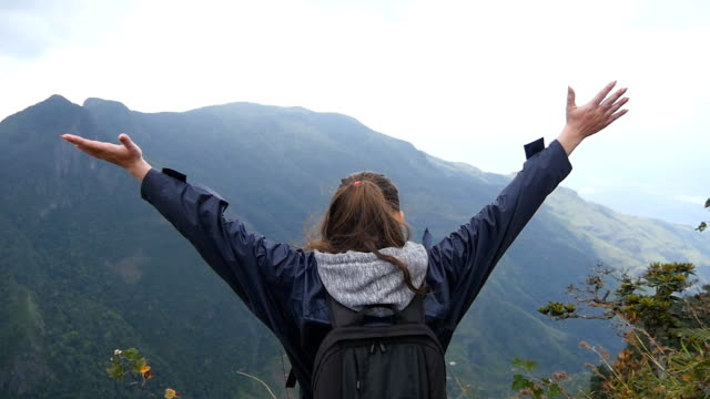Young female hiker with backpack reaching up top of mountain and raised hands. Woman tourist in raincoat standing on the edge of beautiful canyon, victoriously outstretching arms up. Rear back view video