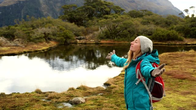 Young female hiking stands by mountain lake and outstretches arms video