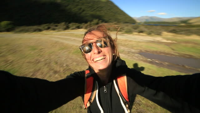 Young female hiking takes selfie portrait with mountains on background video
