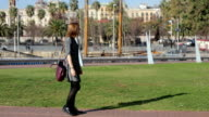 Young female in a dress with red handbag on the background of the barcelona marina park walking with smartphone and meet somebody video