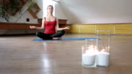 Young female in lotus pose raising hands video