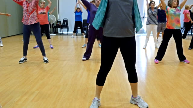 Young female instructor leads yoga class for seniors video