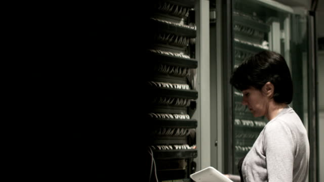 Young female IT engineer working on datacenter servers video
