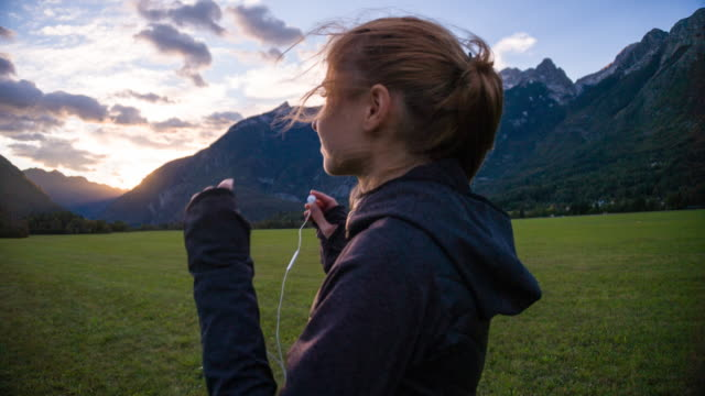 Young female jogger inserting earphones in the mountainside video