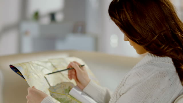 Young female looking for place on map, planning sightseeing tour video
