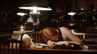 DS Young female medical student falling asleep in library video