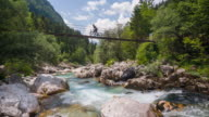 Young female mountain biker riding across a hanging bridge video