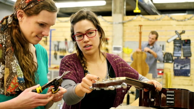 Young female music store manager shows trainee how to restring acoustic guitar video