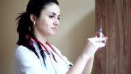 Young female nurse checking the syringe for injection in clinic. Healthcare and medicine concept. Slowmotion video