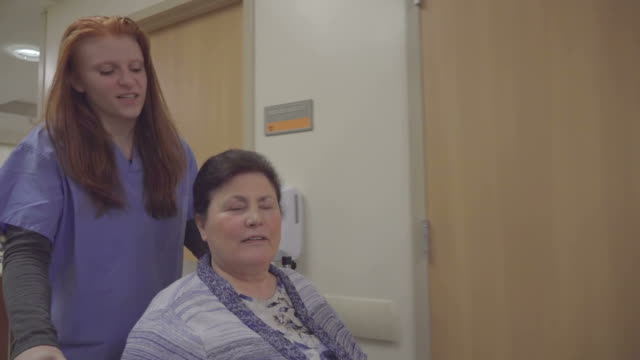 Young Female Nurse Working With Elderly Patient In Hospital video