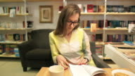 Young female reading a book in a bookstore. video