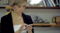 Young female reading sms on the phone in modern office video