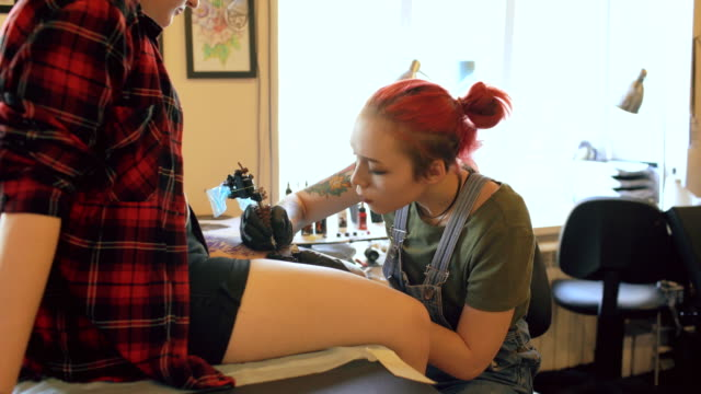 Young female red haired tattoo artist tattooing picture on leg of client over sketch in studio indoors video