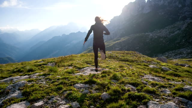 Young female runner running on top of a mountain video