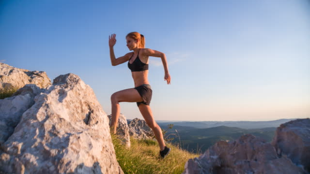 Young female runner running uphill a rocky landscape video