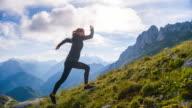 Young female runner running uphill video