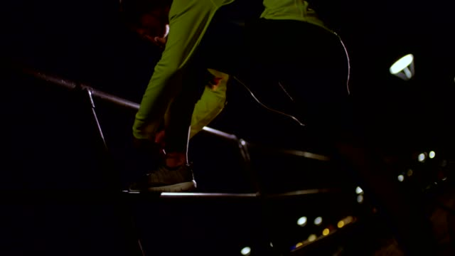 Young female runner tying her shoelaces at night video