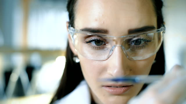 Young female scientist holding test tube with liquid sample making research in clinical laboratory video