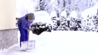 Young female shoveling near own house after snowfall video