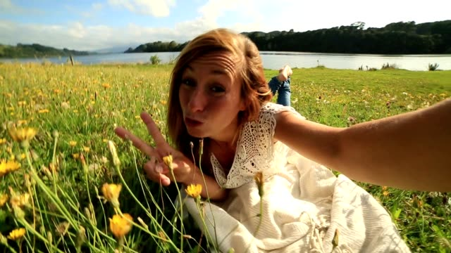 Young female takes a selfie in a wildflower meadow video