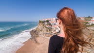 Young female tourist overlooking village on steep cliffs by ocean video