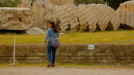 Young female tourist taking picture of huge column remains, sightseeing tour video