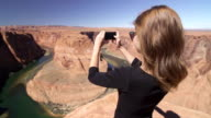 Young female tourist taking pictures of Grand Canyon with smartphone video