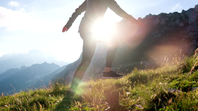 Young female tourist walking up a mountain video