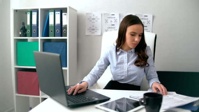 Young female using laptop computer at workplace video