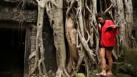 Young female visitor exploring ruins Ta Prohm in Cambodia video