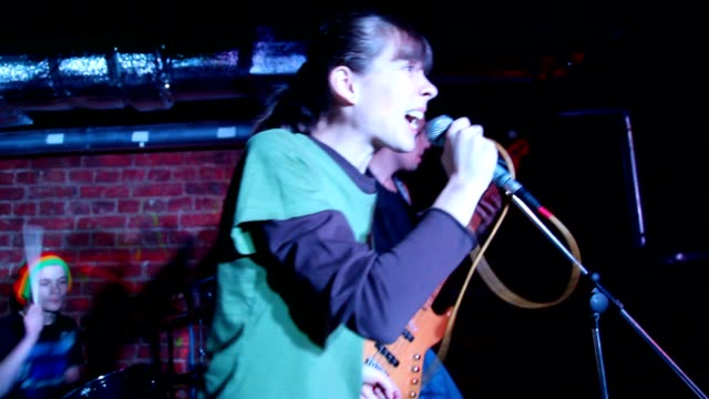 Young female vocalist singing, musicians in background video