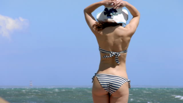 Young female wearing bikini and hat, standing on beach, looking video
