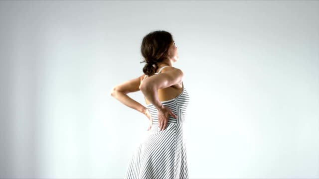 Young female with lower back pain rubbing her back against light background video