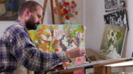 4К Young fine artist holding palette and painting in workshop video