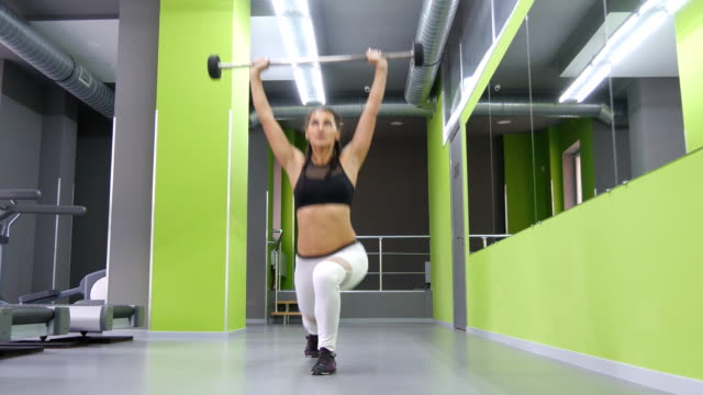 Young fitness woman doing lunge with barbell and flexing muscles in gym. Girl training - attacks with a barbell at health club. Female athlete exercising. Active lifestyle. Close up video