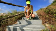 young fitness woman trail runner tying shoelace on mountain stairs video