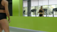 Young fitness woman training in front of the mirror at the gym. Female athlete stretching her body and hands before workout. Girl exercisers in health club. Close up video
